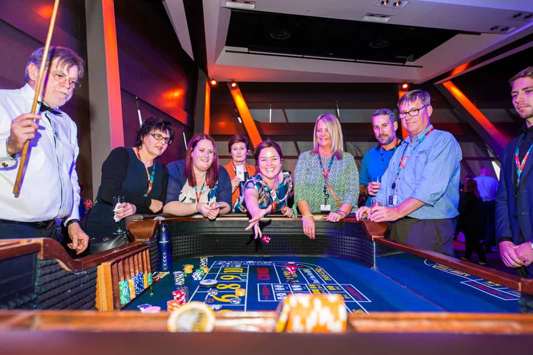 People playing craps at a conference welcome event.