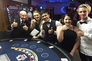 people at a casino party hire night around a blackjack table
