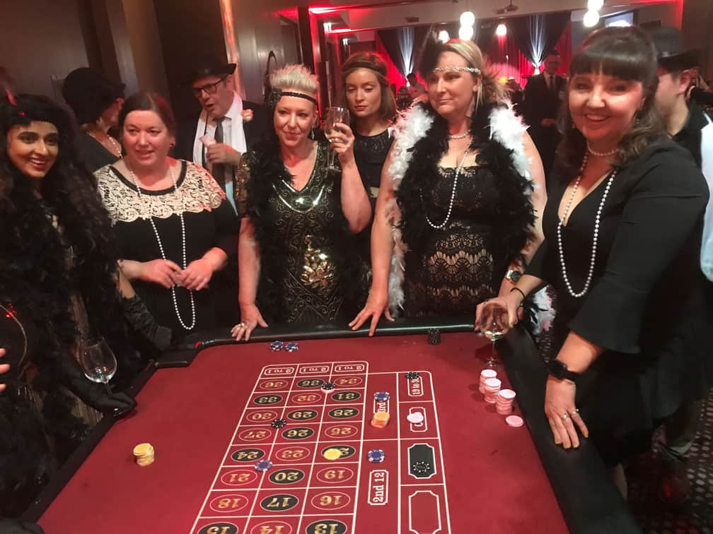 People around a roulette table at a conference